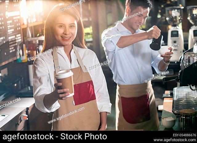 Portrait of asian barista hold take away coffee cup and serving to customer in cafe with other barista working in background