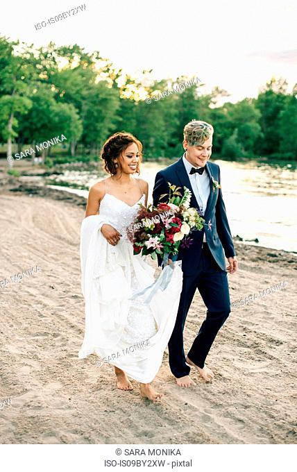 Romantic bride and groom strolling barefoot on lakeside, Lake Ontario, Toronto, Canada