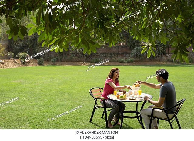 Man and woman having breakfast outside