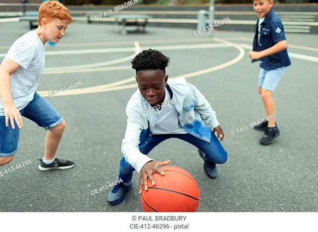 Tween boys playing basketball in schoolyard