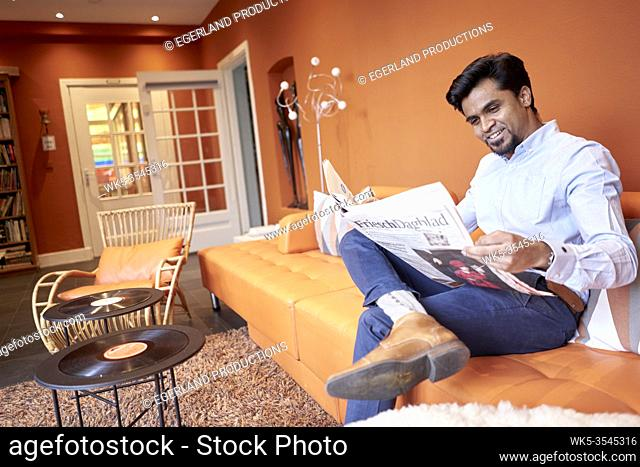 Indian businessman reading newspaper in lobby