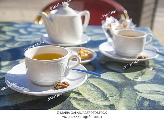 Two cups of tea with biscuits in a terrace