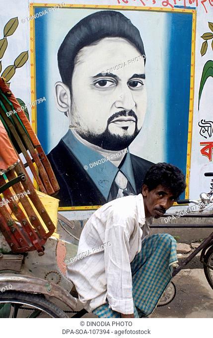 Cycle  Rickshaw Rider sitting Near at Wall Painting of Political Graffiti ; Dhaka  ; Bangladesh