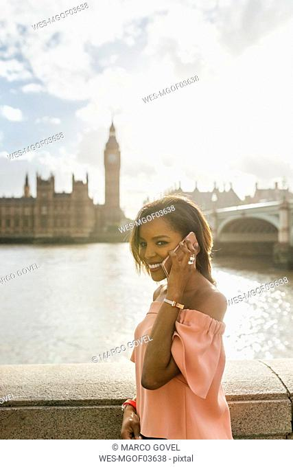 UK, London, woman talking on the phone near Westminster Bridge