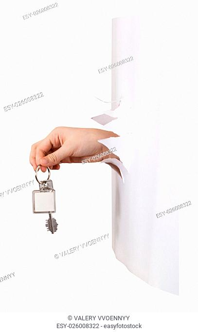 side view of hand holds the keyring through a hole in a sheet of paper isolated on white background