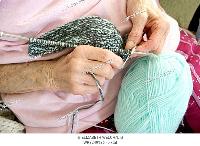 Elderly woman knitting a garment