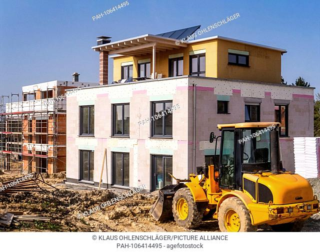 A new building next to a shell in a construction area with a wheel loader in the foreground | usage worldwide. - Oberursel/Hessen/Germany