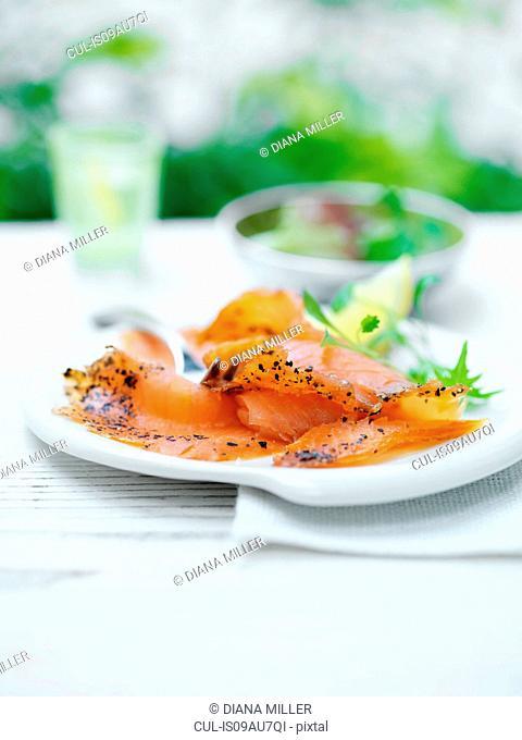 Deli salmon, with sliced lemon and green salad leaves