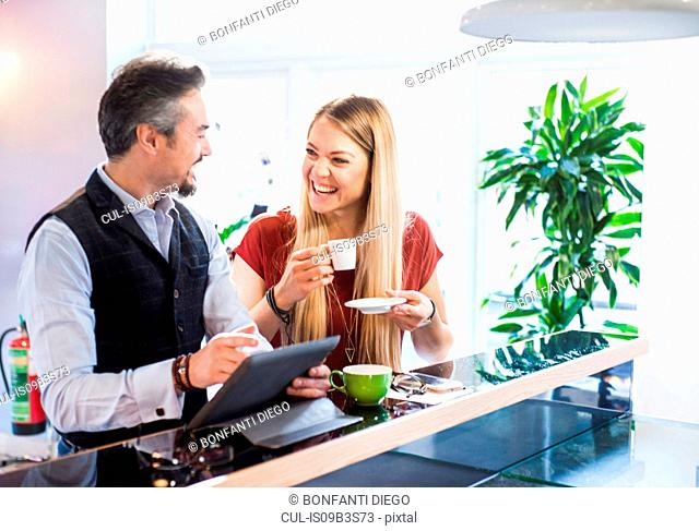 Businessman and woman laughing during coffee break in office