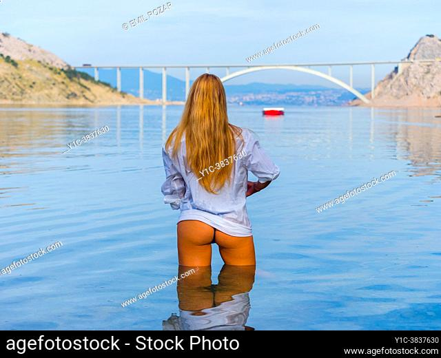 Sexy teenage girl standing in shallow sea view from back