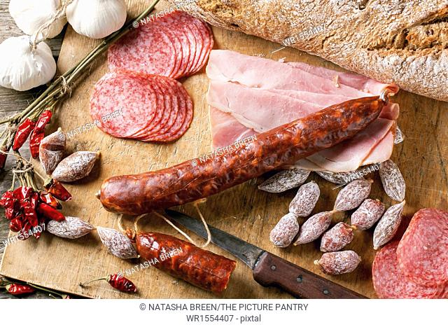 Top view on set of ham and salami served with red hot chili peppers on wooden cutting board