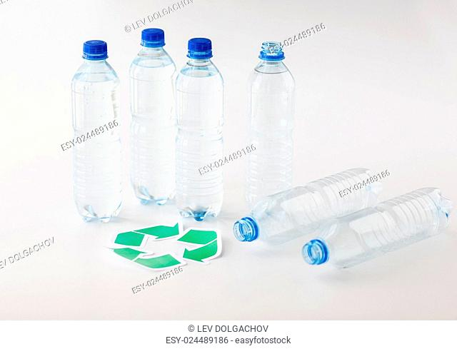 recycling, reuse, garbage disposal, environment and ecology concept - close up of plastic water bottles with green recycle symbol on table