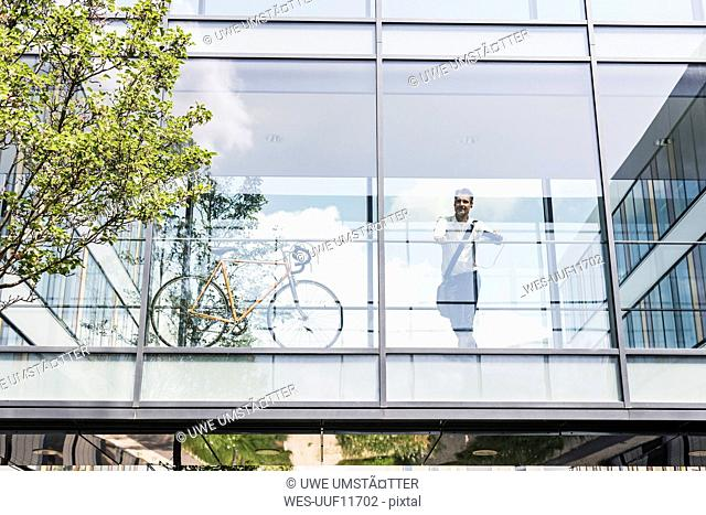 Businessman with bicycle in office passageway