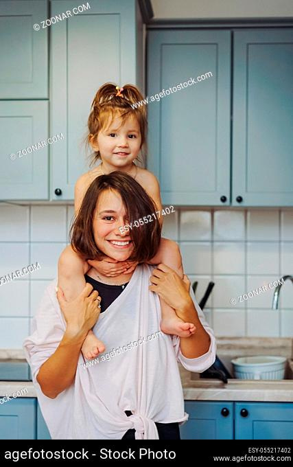 beautiful little daughter piggybacking on her happy mother in the kitchen