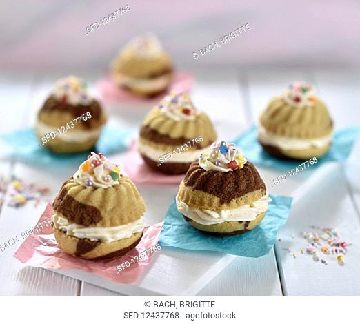 Mini marble gugelhupfs filled with vanilla cream and sprinkled with colourful sugar pearls (vegan)
