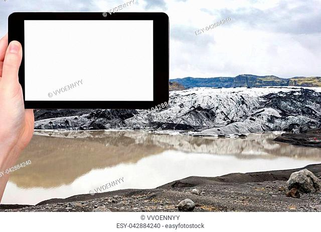 travel concept - tourist photographs Solheimajokull glacier (South glacial tongue of Myrdalsjokull ice cap) in Katla Geopark in Iceland in autumn on tablet with...