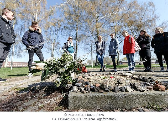 15 April 2019, Hamburg: During a tour of the grounds of the former Neuengamme concentration camp, pupils of a 9th grade stand at the memorial plaque of the...