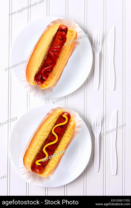 Top view of an all white place setting with hot dogs one with ketchup, one with mustard