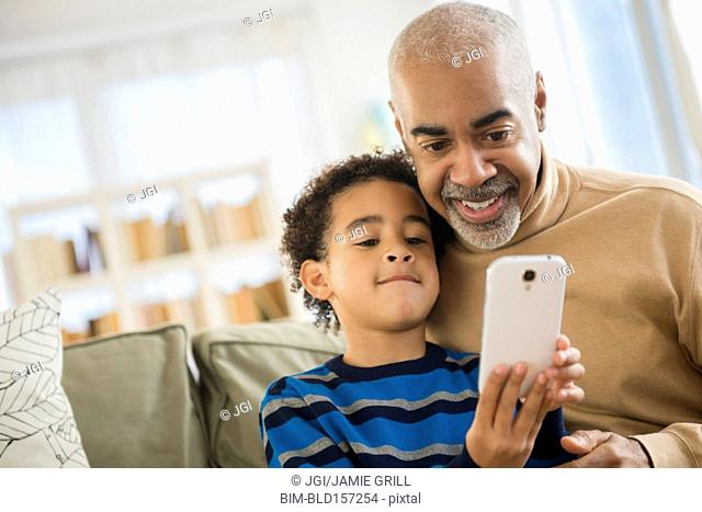 Mixed race grandfather and grandson using cell phone