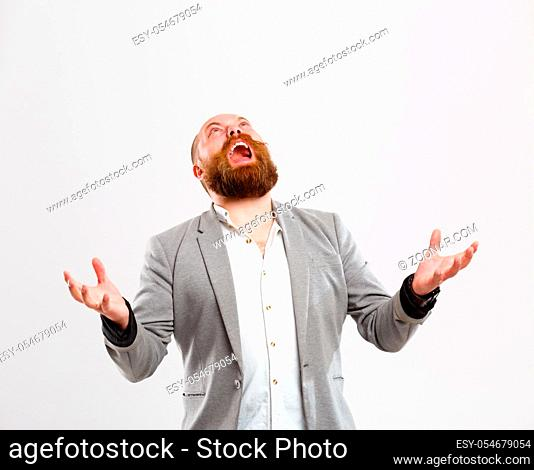 Disgruntled screaming man looking up, with ginger beard in gray jacket on empty background