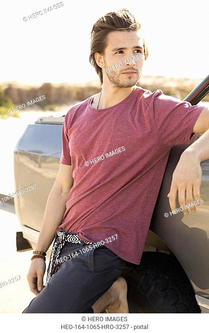 Man leaning against vehicle