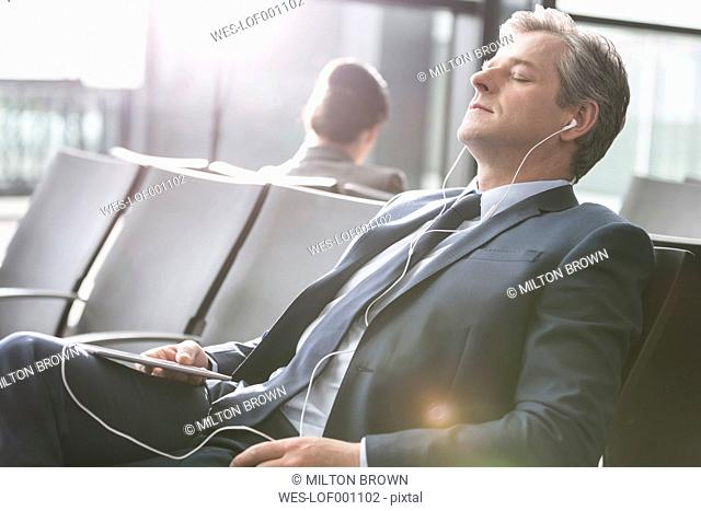 Relaxed businessman with earbuds and digital tablet at the airport