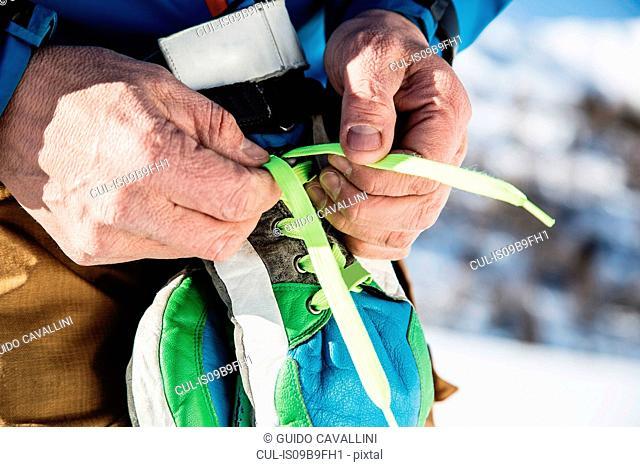 Skier tying laces on ski gloves, close-up