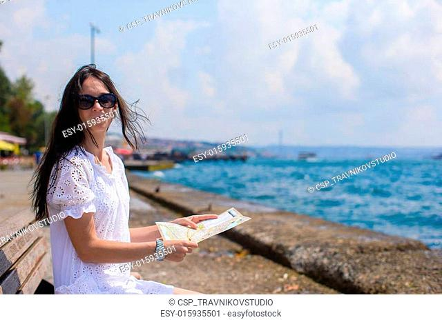 Beautiful girl with map of the island while riding bicycle