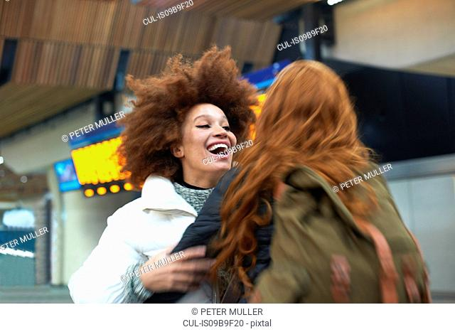 Two young women greeting each other at train station