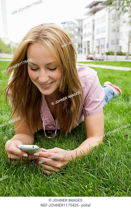Portrait of woman lying on grass and using mobile phone