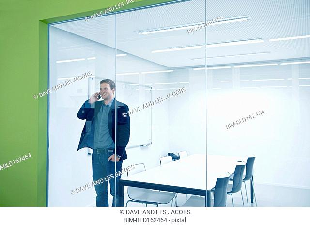 Caucasian businessman talking on cell phone in conference room
