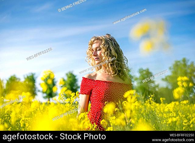 Woman wearing red dress with eyes closed standing amidst oilseed rapes