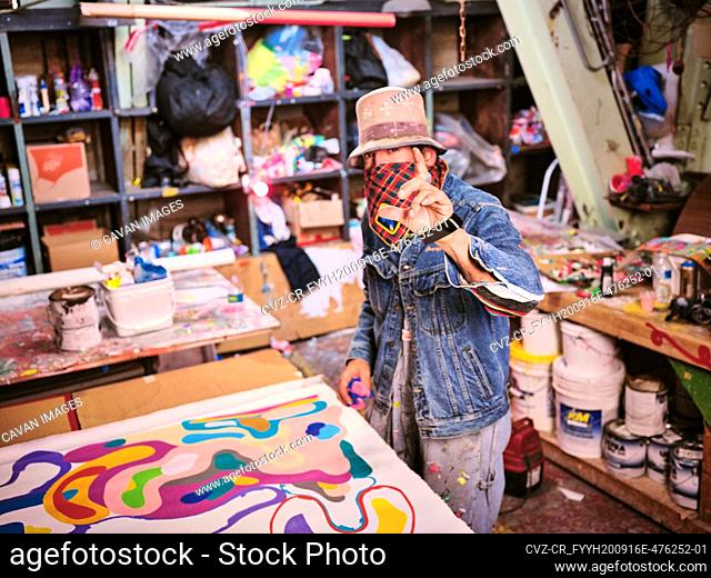 An artist with face covering works in their art studio