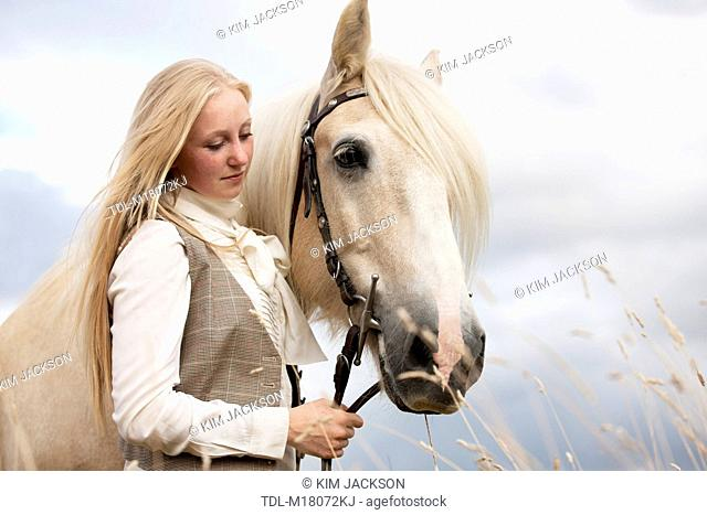 A young woman standing with a palomino horse