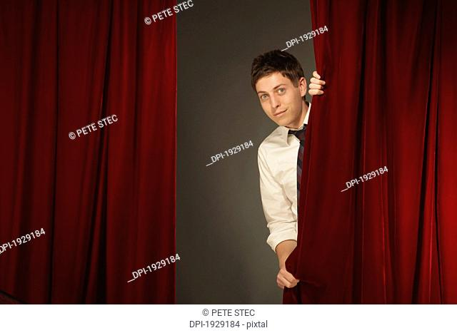 man peeking from behind a red stage curtain