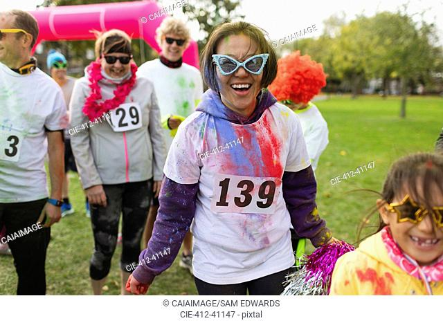 Portrait smiling, playful female runner in silly sunglasses at charity run in park