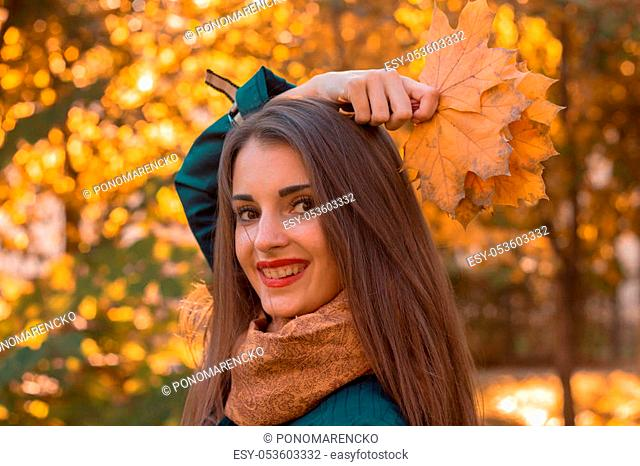 beautiful charming girl who keeps the leaves above her head and smiles at krupnyy plan