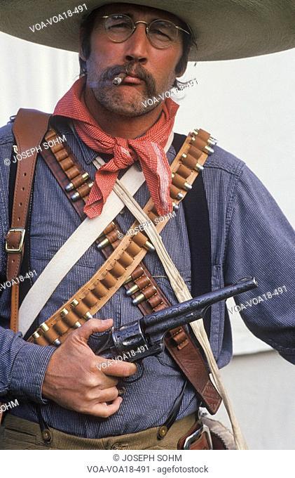 Portrait of Old West gunslinger participant with pistols, CA