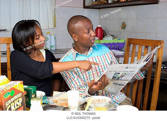 Kenyan couple reading paper at breakfast time, Nairobi, Kenya