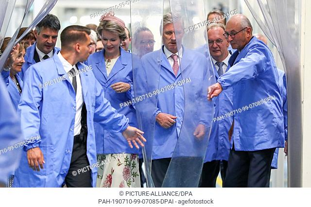 10 July 2019, Saxony-Anhalt, Leuna: Jan De Clerck (r), owner of the Domo chemical company, opens a plastic curtain for the Belgian royal couple King Philippe...