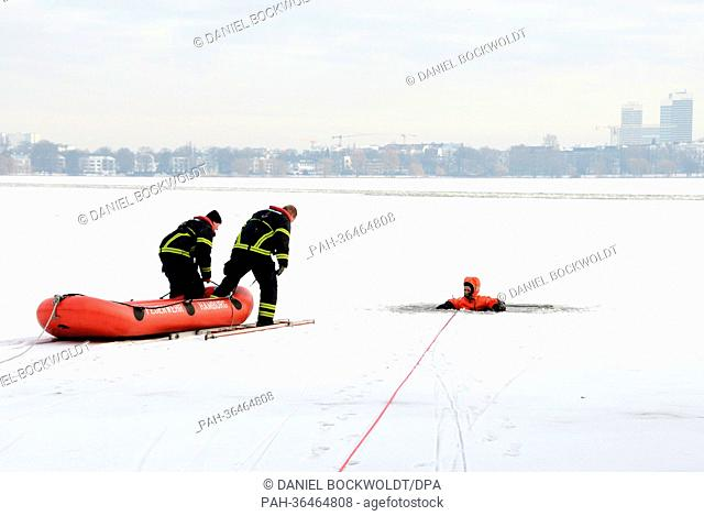Firefighters conduct a drill in which they rescue a woman who broke through the ice of the Alster in Hamburg, Germany, 25 January 2013