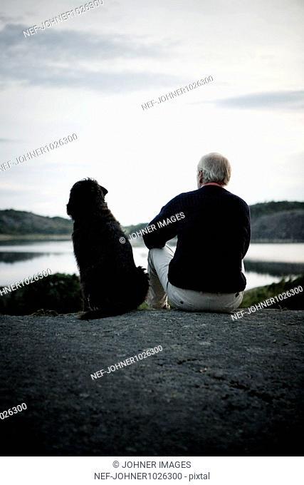 Sweden, Bohuslan, senior man with dog relaxing near lake