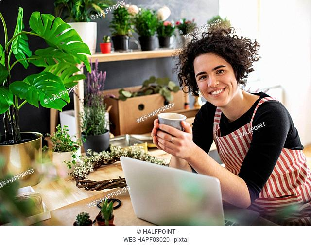 Portrait of smiling young woman with coffee mug and laptop in a small shop with plants