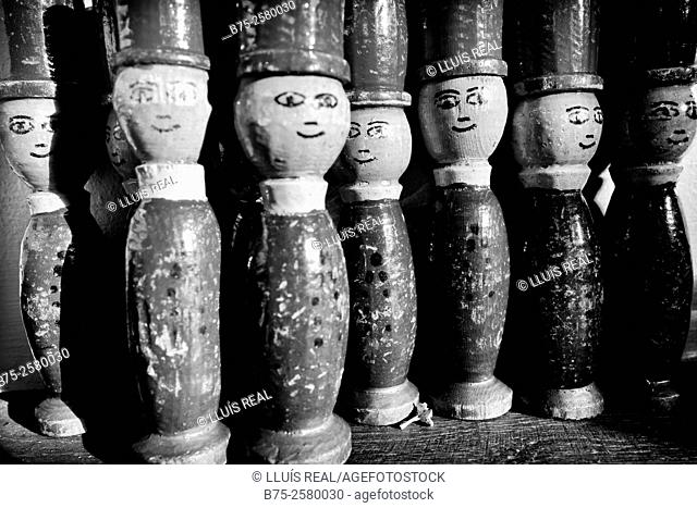 Group of wooden dolls of a child vintage game looking at the camera