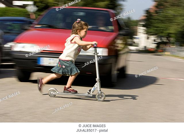 Young girl riding push scooter in road in front of car