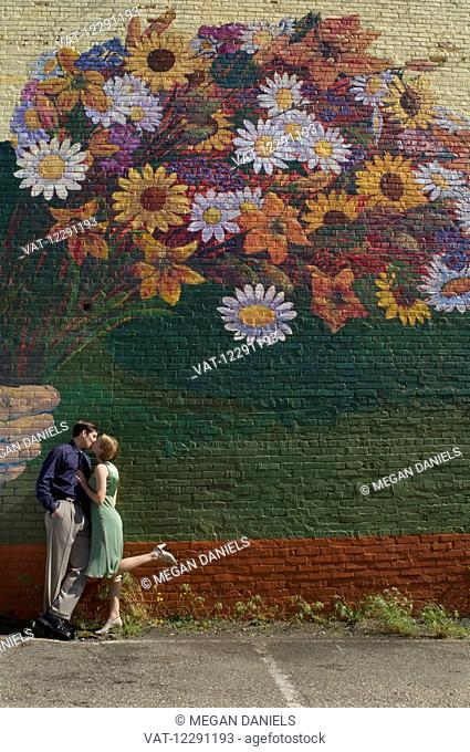 A couple kisses as they lean against a wall with a large mural of a colourful bouquet of flowers painted on the wall; Raleigh, North Carolina