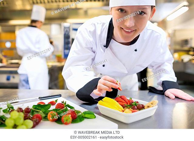 Happy chef preparing fruit salad in kitchen