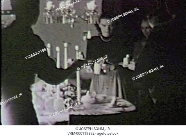 Black and white footage of midwestern birthday party wish fully dressed adults serving desert
