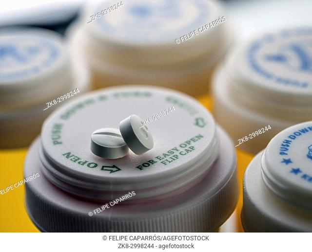 Two white pills on a plastic pill bottle, conceptual image
