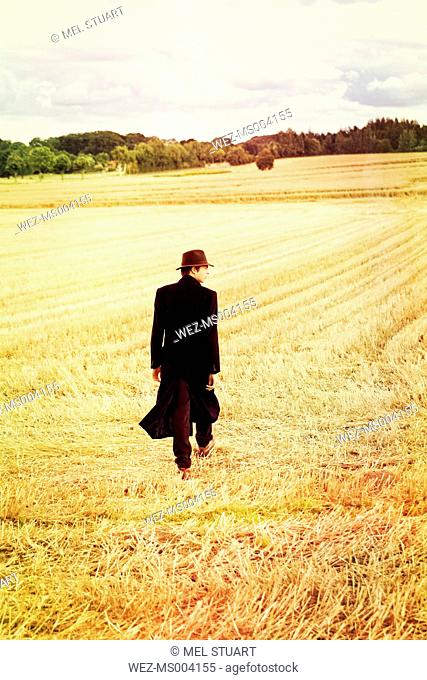Teenage boy with hat and coat walking on stubble field